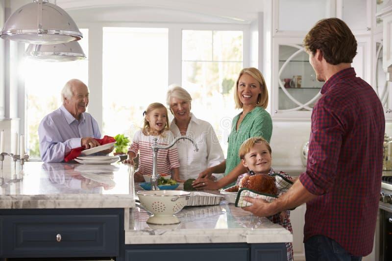 De familie met Grootouders maakt de Maaltijd van Braadstukturkije in Keuken stock foto