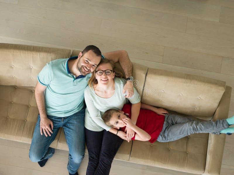 De familie met weinig jongen geniet van in de moderne woonkamer stock foto's
