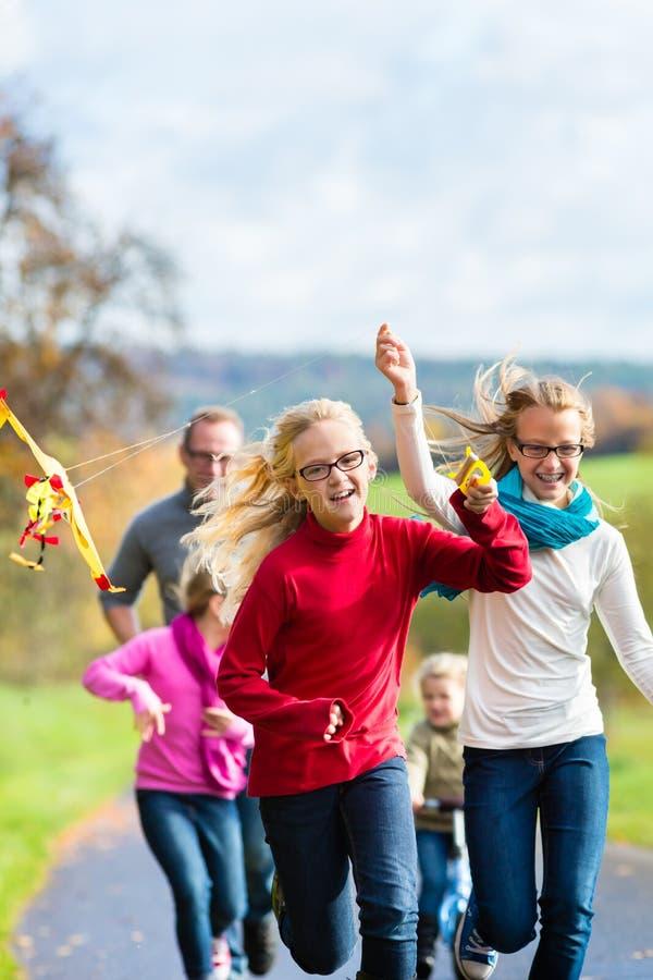 De familie neemt gang in de herfst bos vliegende vlieger royalty-vrije stock foto's