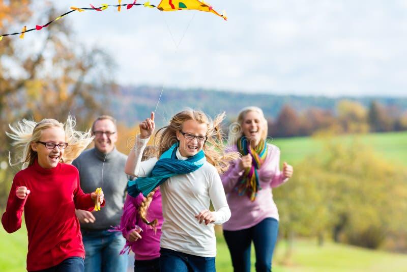 De familie neemt gang in de herfst bos vliegende vlieger royalty-vrije stock foto