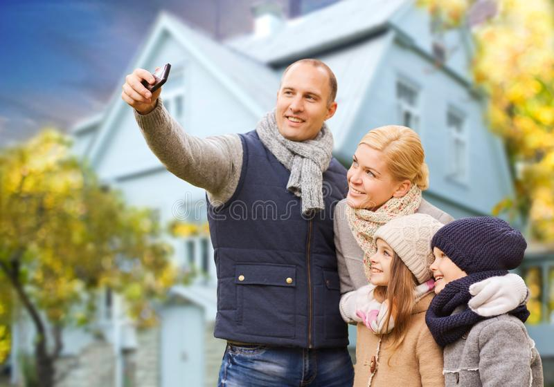 De familie neemt de herfst selfie door cellphone over huis royalty-vrije stock fotografie