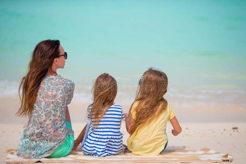 De familie op het strand ontspant en bekijkend de horizon Het mamma en de jonge geitjes genieten van Europese vakantie royalty-vrije stock afbeeldingen