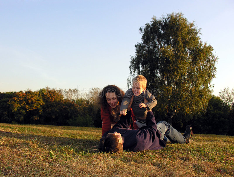 De familie speelt de herfst op zonsondergang op open plek royalty-vrije stock afbeeldingen
