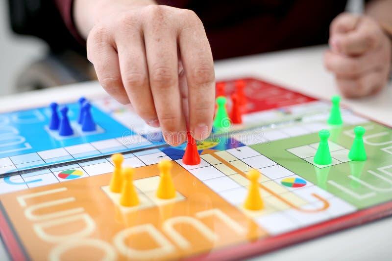 De familie speelt de raadsspel die van Ludo samen heel wat pret hebben stock afbeelding