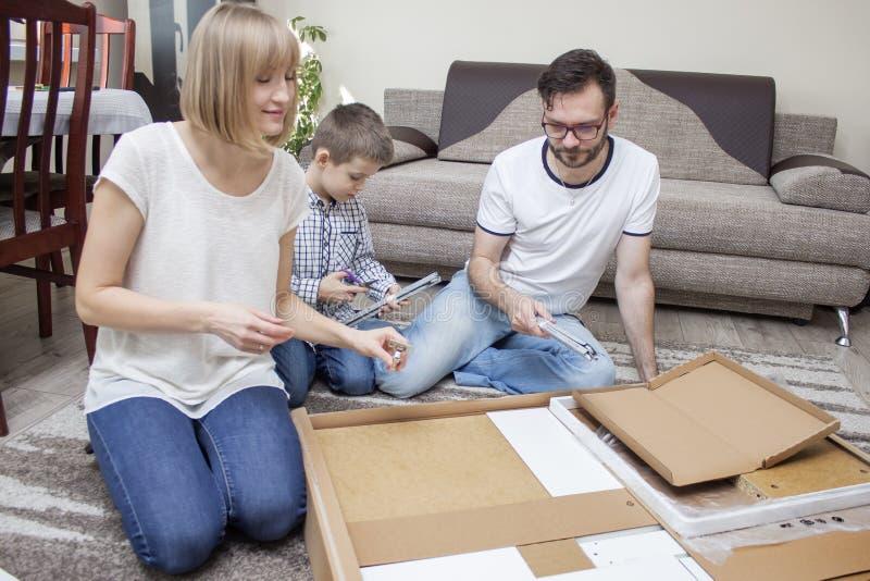 De familie uit mamma, papa en jongen wordt samengesteld draait meubilair op het tapijt die pret hebben die royalty-vrije stock foto