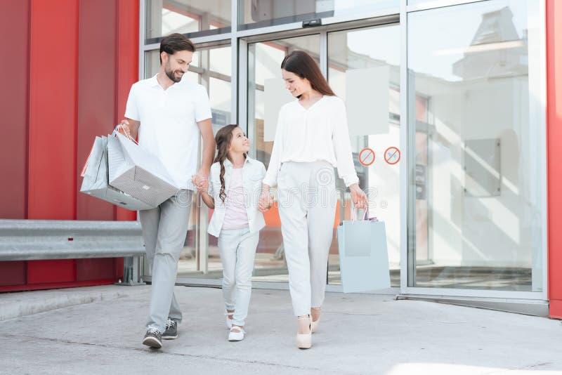 De familie, de vader, de moeder en de dochter verlaten winkelcomplex met aankopen royalty-vrije stock afbeeldingen