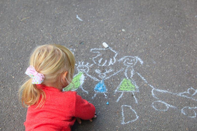 De familie van de meisjetekening met krijt op asfalt stock foto