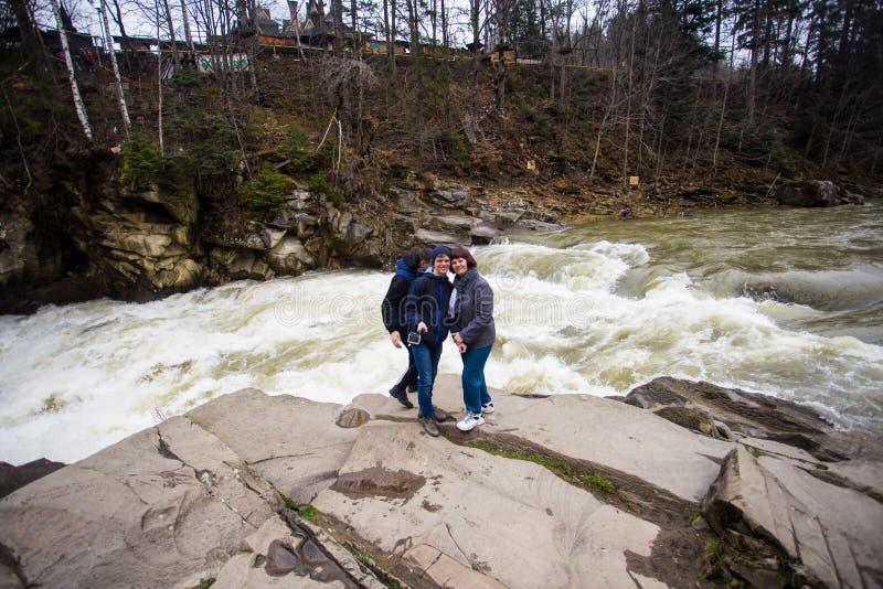 De familie van drie loopt dichtbij rivier na aard wandeling Mensen die op rots in bosrivier rusten die de lente van dag genieten stock foto's
