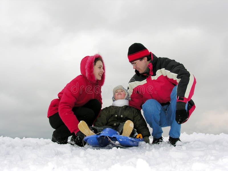 De familie van drie zit. de winter stock foto