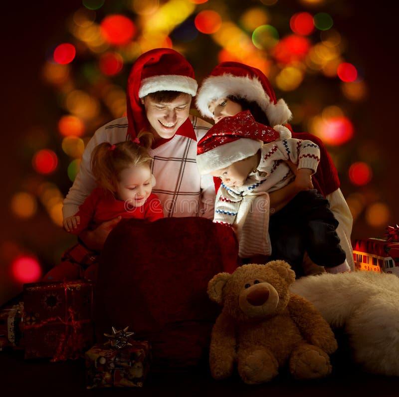 De familie van Kerstmis in rode hoeden met wi van de giftzak royalty-vrije stock afbeeldingen