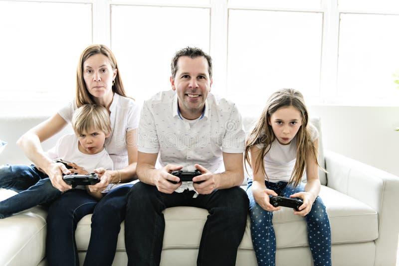 De familie van vier die pret op de bank hebben speelt thuis videospelletje royalty-vrije stock fotografie