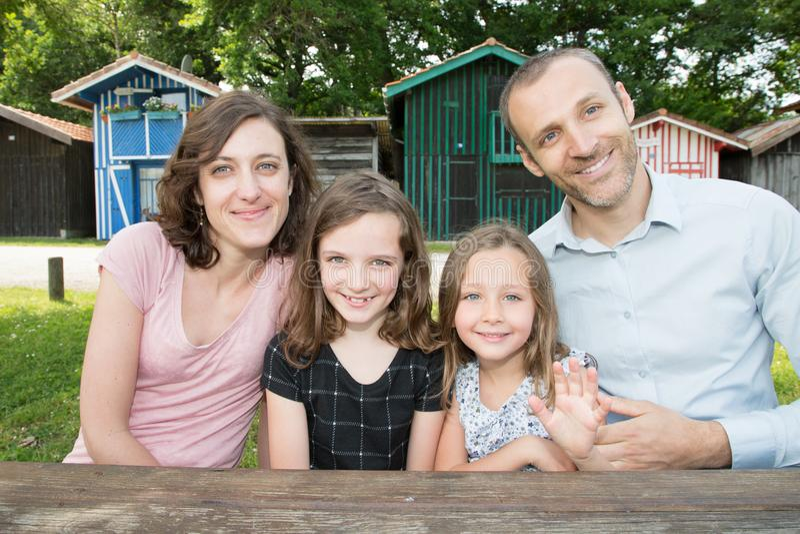 De familie van vier zit op houten lijst aangaande park in de dag van de de zomerlente stock foto