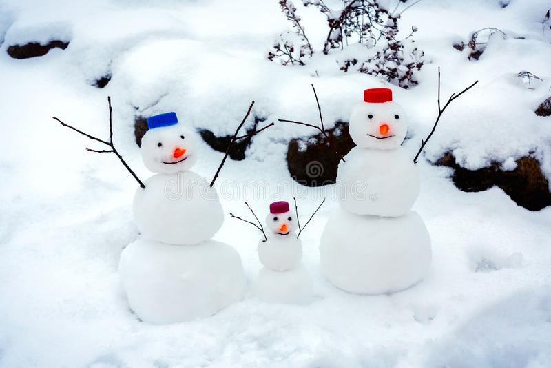 De familie van vrolijke sneeuwmannen verheugt zich bij de aankomst van de winter en de eerste sneeuw royalty-vrije stock foto