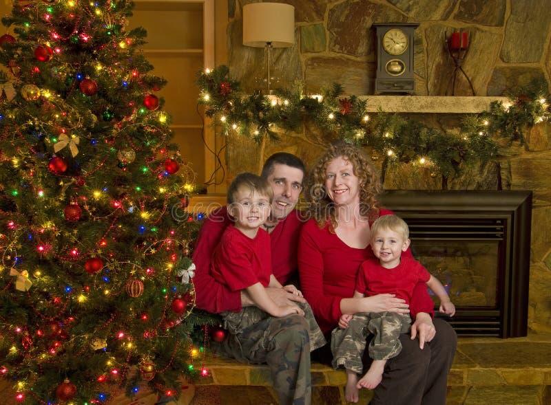 De familie zit naast Kerstboom stock afbeeldingen