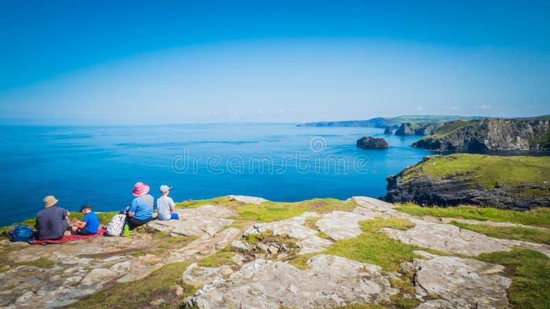 De familie zit op een klip bij Tintagel-kasteel in Cornwall, Engeland met de kustlijn van de Atlantische Oceaan stock foto