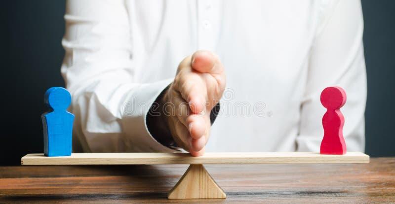 De familieadvocaat deelt het cijfer van een man en een vrouw op schalen Het concept scheiding en afdeling van bezit solving stock foto
