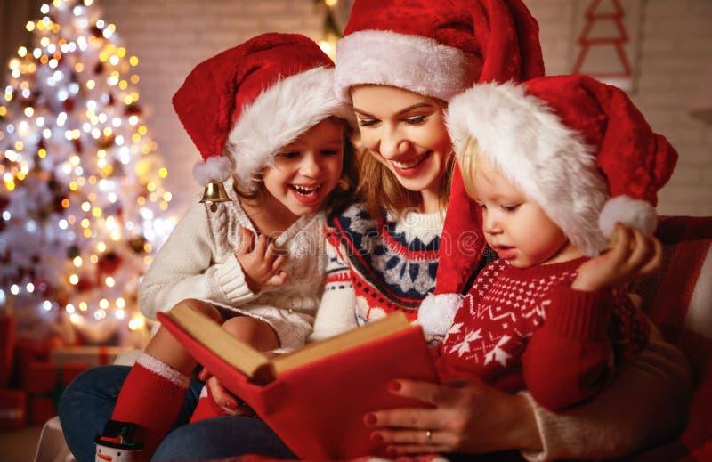 De de familiemoeder en kinderen lezen een boek dichtbij bij Kerstmis firep royalty-vrije stock foto