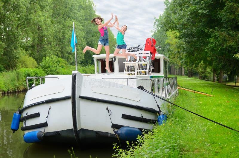 De familievakantie, reis op aakboot in kanaal, gelukkige ouders met jonge geitjes op riviercruise haalt in woonboot over stock afbeeldingen