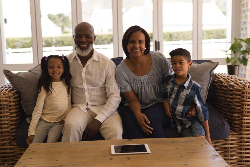 De familiezitting van meerdere generaties op bank in woonkamer royalty-vrije stock foto