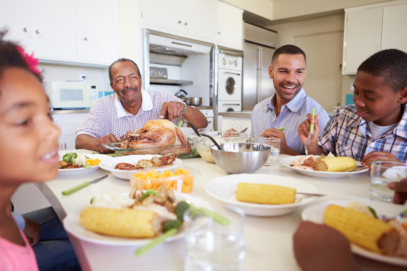 De Familiezitting van meerdere generaties rond Lijst die Maaltijd eten royalty-vrije stock afbeeldingen