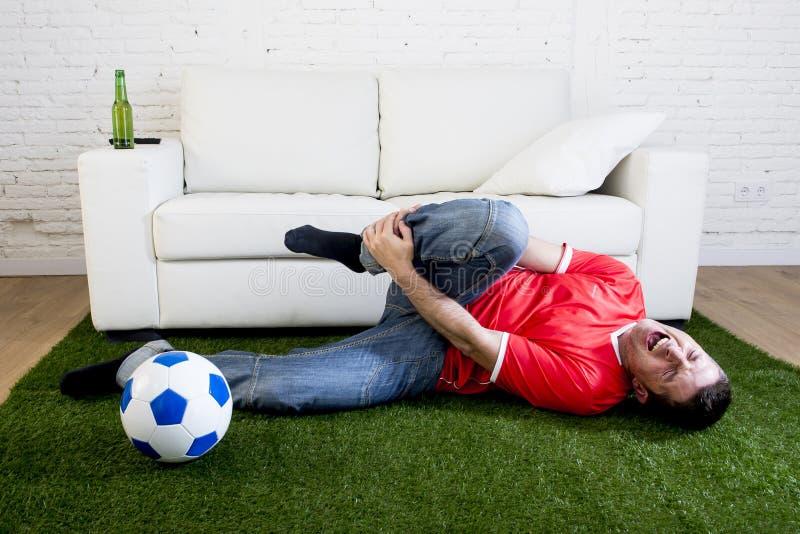 De fanatieke voetbalventilator op groen grastapijt die de hoogte bespottende speler van het voetbalstadion in pijn nastreven kwet stock afbeelding
