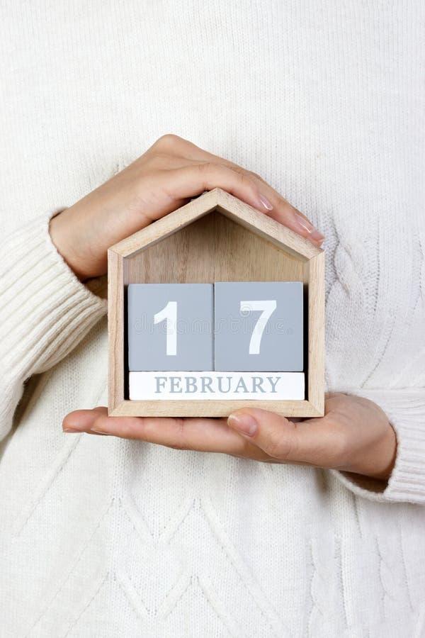17 de febrero en el calendario la muchacha está sosteniendo un calendario de madera Actos al azar del día de la amabilidad fotos de archivo libres de regalías