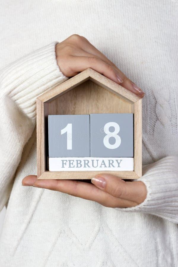 18 de febrero en el calendario la muchacha está sosteniendo un calendario de madera Día del mundo para la protección de Marine Ma fotos de archivo libres de regalías
