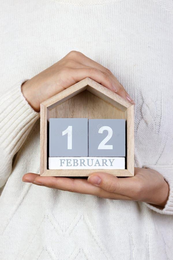 12 de febrero en el calendario la muchacha está sosteniendo un calendario de madera Día internacional de agencias de la boda, día imágenes de archivo libres de regalías