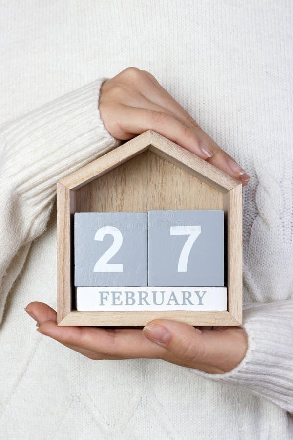 27 de febrero en el calendario la muchacha está sosteniendo un calendario de madera Día internacional del oso polar, el principio imagenes de archivo