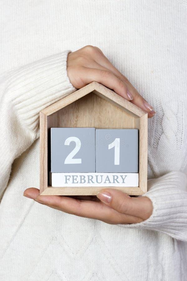 21 de febrero en el calendario la muchacha está sosteniendo un calendario de madera Día internacional de la lengua de madre, guía imagen de archivo