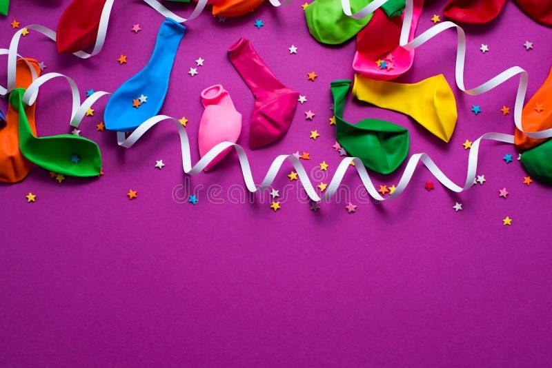 De feestelijke achtergrond van de purpere materiële kleurrijke vlakte van de de confettien Hoogste mening van ballonswimpels legt stock foto