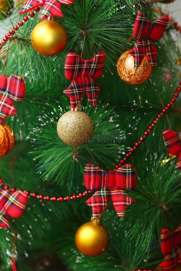 De feestelijke dichte omhooggaande Kerstboom verticale achtergrond met gouden en schitterende snuisterijen en geruit Schots wolle royalty-vrije stock foto