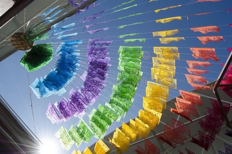 De feestelijke kleurrijke banners hangen met openluchtlichten tegen een heldere blauwe hemel stock fotografie