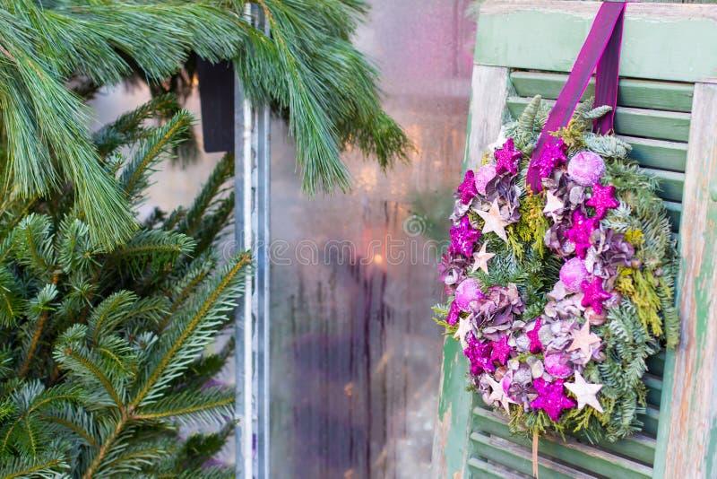 De feestelijke kroon van de Kerstmiskomst hangt buiten bij groene houten poortenachtergrond spar op achtergrond, plaats voor teks royalty-vrije stock afbeelding