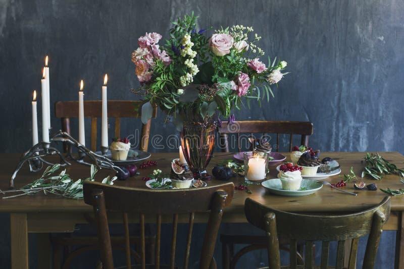 De feestelijke lijst die met bloemboeket plaatsen, kaarsen en dess royalty-vrije stock afbeelding