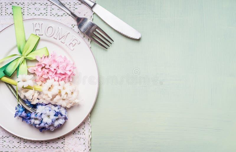 De feestelijke lijstplaats die met hyacinten plaatsen bloeit decoratie, plaat, vork en mes op lichtgroene achtergrond, hoogste me royalty-vrije stock foto