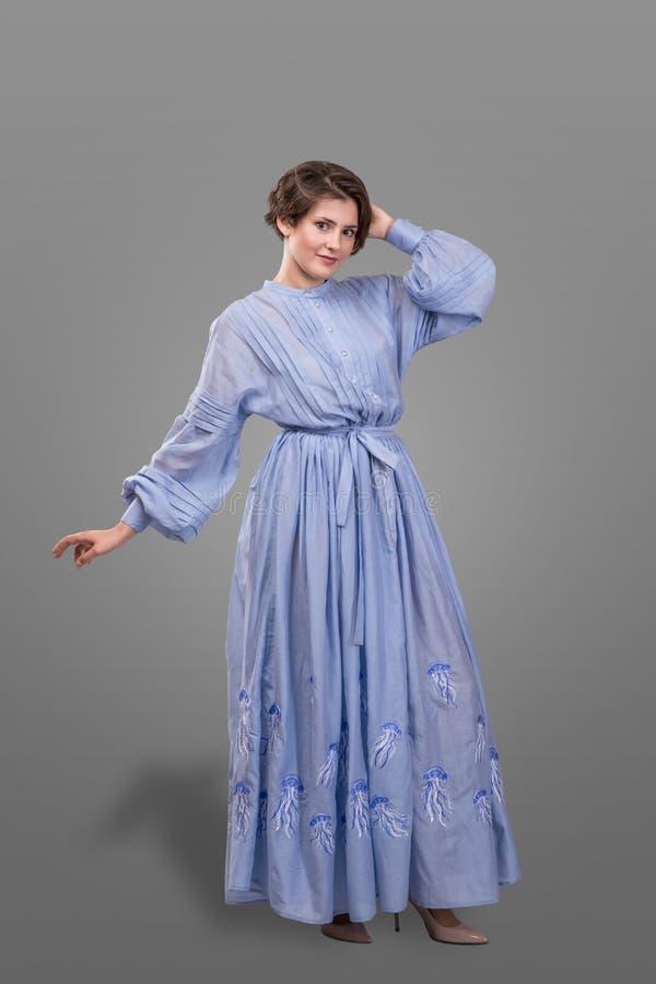 De Femail del modelo del desgaste vestido azul de largo sobre fondo gris fotografía de archivo
