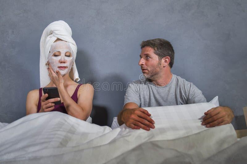 De femme au foyer excentrique et étrange avec le masque et la serviette faciaux de maquillage utilisant le téléphone portable dan photo stock