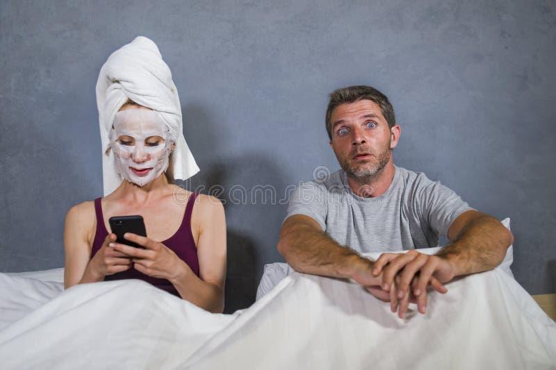 De femme au foyer excentrique et étrange avec le masque et la serviette faciaux de maquillage utilisant le téléphone portable dan photographie stock