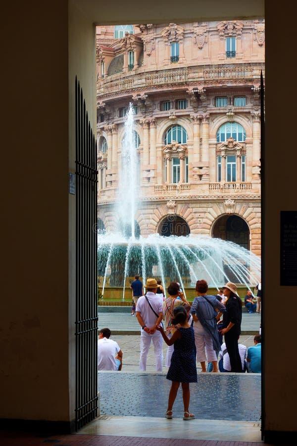 De Ferrari square in Genoa. Genoa Genova, Italy - July 7, 2019: De Ferrari square in Genoa with the fountain and walking people through the doorway stock photography