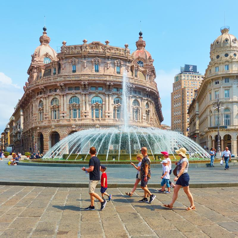 De Ferrari square in Genoa and walking people. Genoa Genova, Italy - July 7, 2019: De Ferrari square in Genoa with the fountain and walking people royalty free stock photos