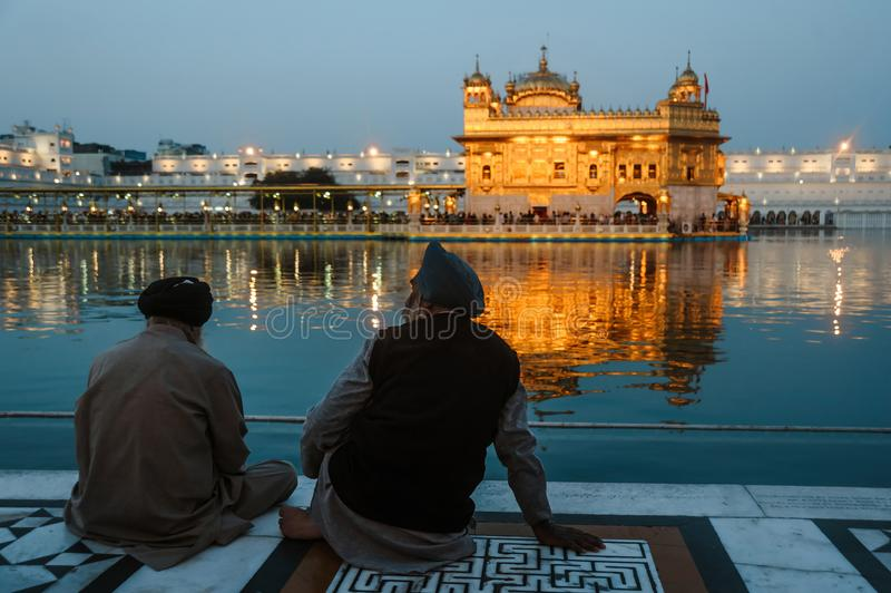 24 de fevereiro de 2018 Amritsar, Índia Dois sikhs indianos equipam sentam-se perto da água do templo dourado na noite foto de stock royalty free