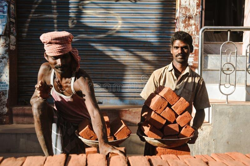 23 de fevereiro de 2018 Madurai, Índia, dois trabalhadores indianos dentro fora com ful das placas dos tijolos imagem de stock royalty free