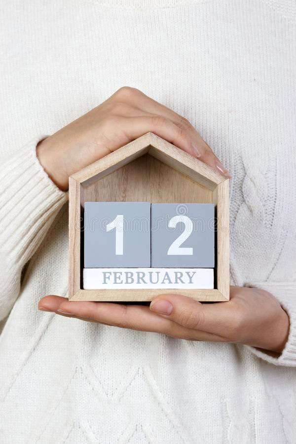 12 de fevereiro no calendário a menina está guardando um calendário de madeira Dia internacional de agências da união, dia de Abr imagens de stock royalty free