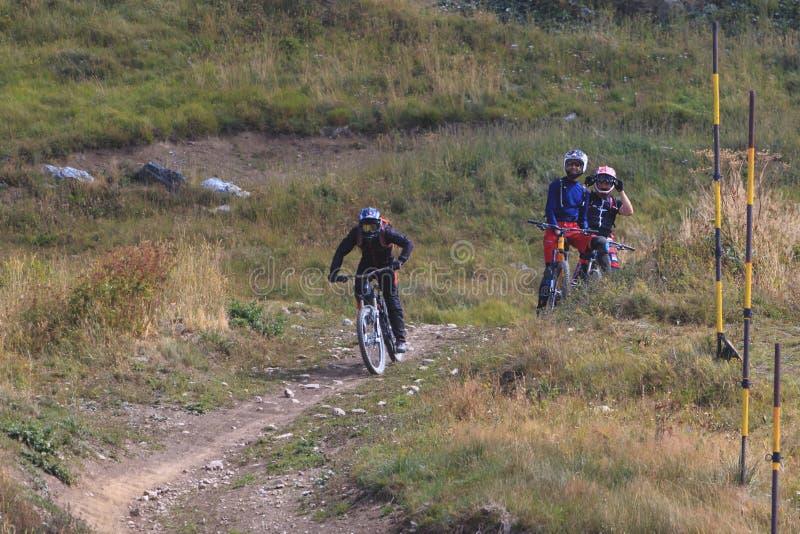 De fiets van de personenvervoerberg bergaf en twee vrienden die op hem letten royalty-vrije stock afbeeldingen