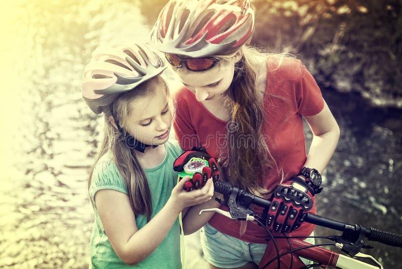 De fietsen die kinderenmeisje cirkelen die helm dragen bekijken kompas royalty-vrije stock afbeeldingen
