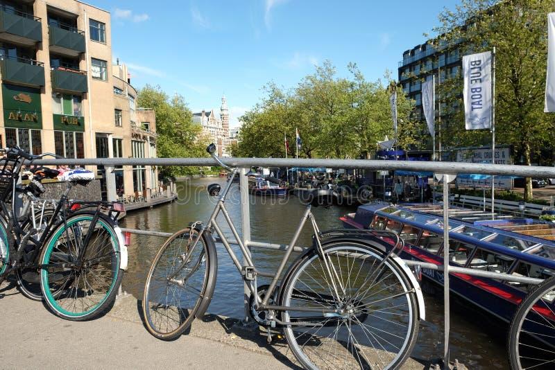De fietsen worden geparkeerd aan het traliewerk van de brug in Amsterdam royalty-vrije stock afbeelding