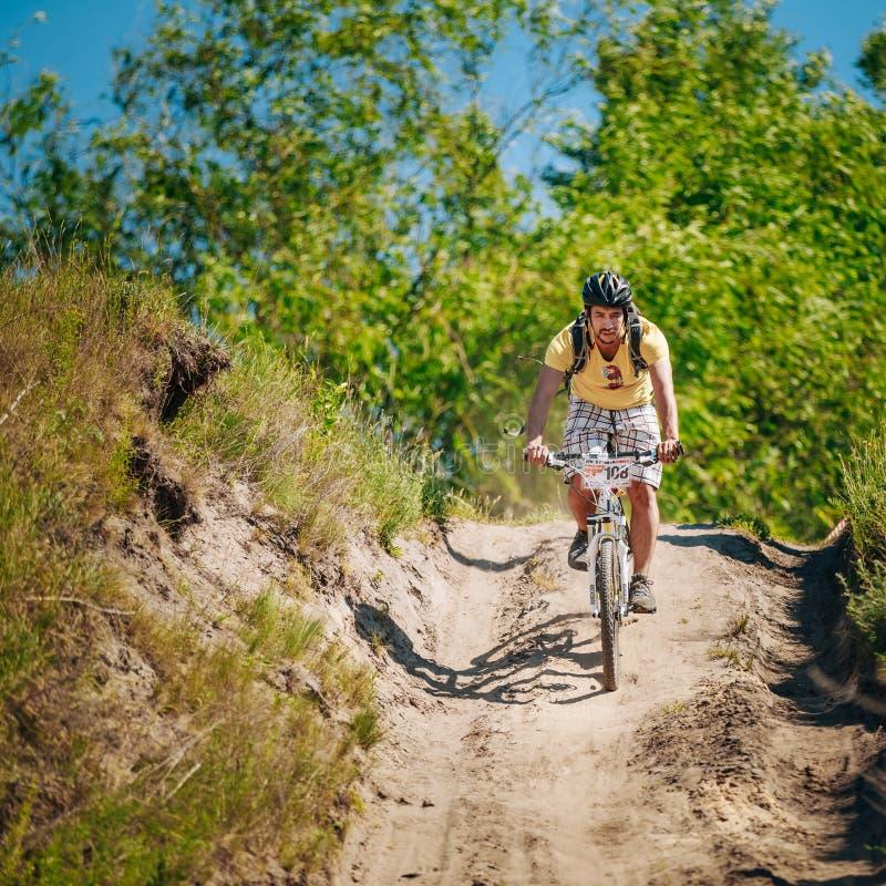 De fietser berijdend spoor van de bergfiets bij zonnige dag stock fotografie