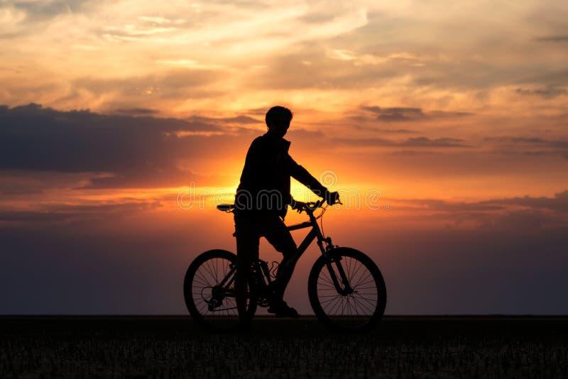 De fietser bewondert de zonsondergang stock foto