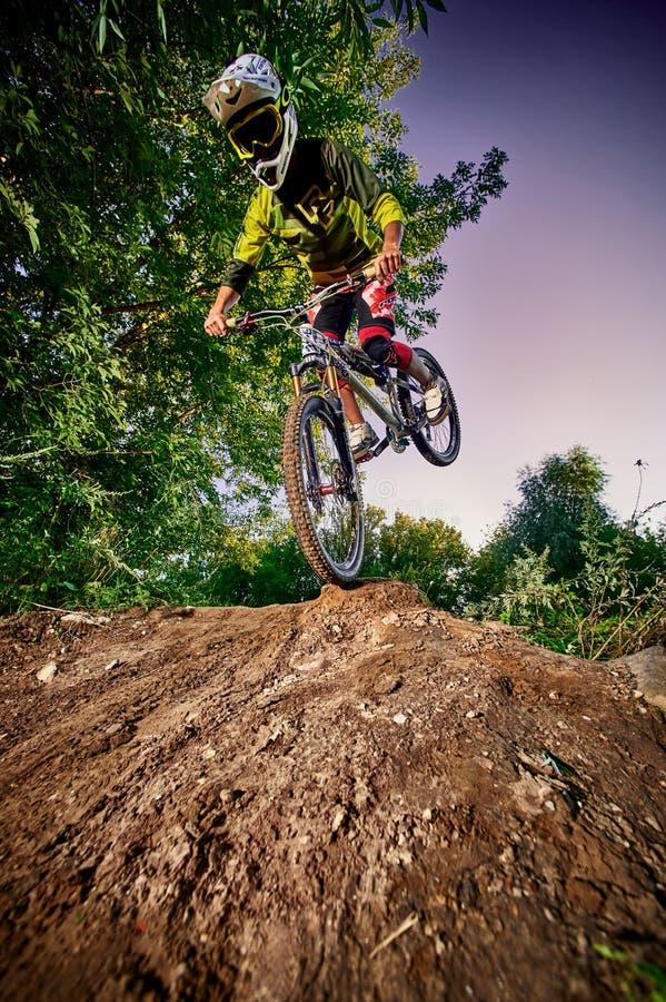 De fietser die van de bergfiets stoppie, bereden op het voorwiel doen royalty-vrije stock afbeeldingen
